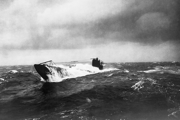 This is a gray scale image that shows a u-boat emerging from a dark body of water.