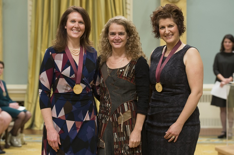 Two teachers wearing medals pose with the Governor General (centre)